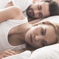 Woman laying awake with sleep partner next to her