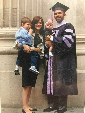Dr. Milner in a graduation cap and gown with his family
