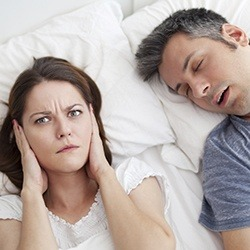 Woman covering ears next to snoring man