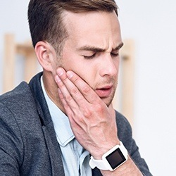 Man grimacing holding cheek in pain