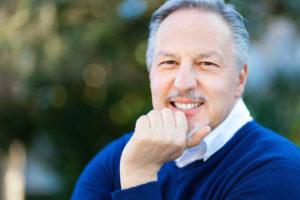older man smiling outdoors