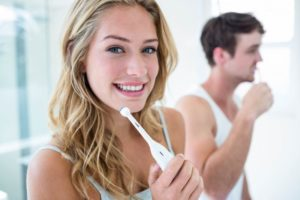 Couple brushing teeth using tips from dentist