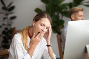 Woman tired from sleep apnea at computer
