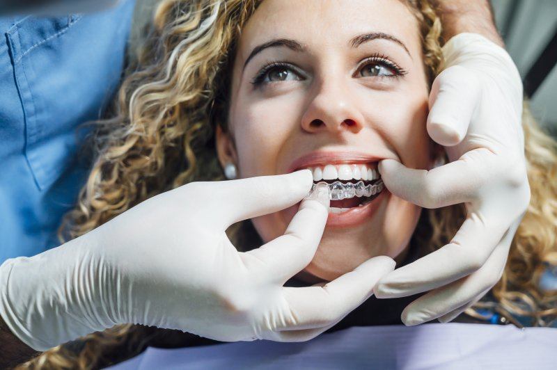 Dentist helping patient put on Invisalign