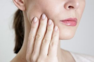 Woman experiencing pain due to loose tooth